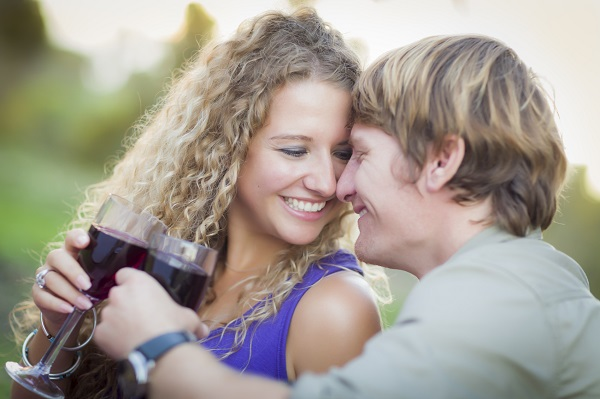 An Attractive Couple Enjoying A Glass Of Wine in the Park Together.